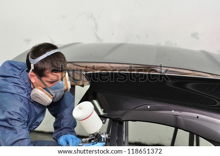 Worker painting car parts. - stock photo