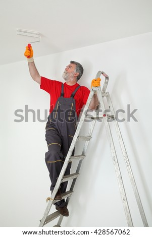 Worker painting ceiling with paint roller from ladder