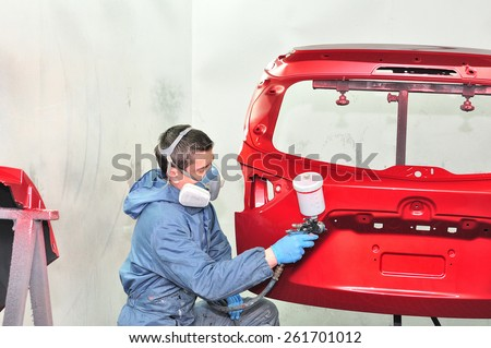 Worker painting red car part. - stock photo