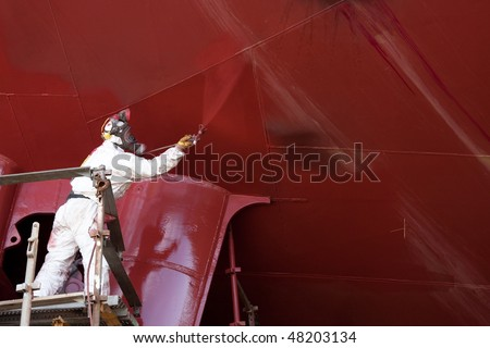 worker painting ship hull using airbrush red paint - stock photo