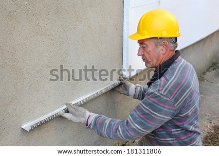 Worker placing aluminum batten for styrofoam sheet insulation to the wall