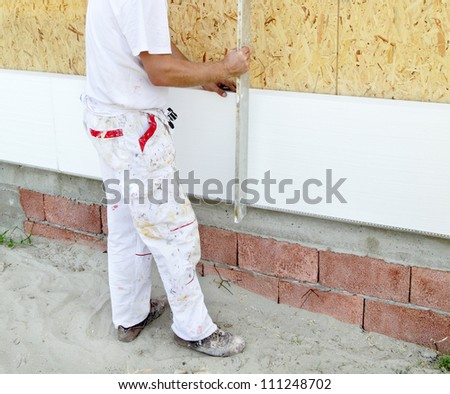 Worker placing styrofoam sheet insulation using level tool - stock photo