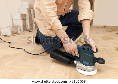 worker polishes oak parquet - stock photo