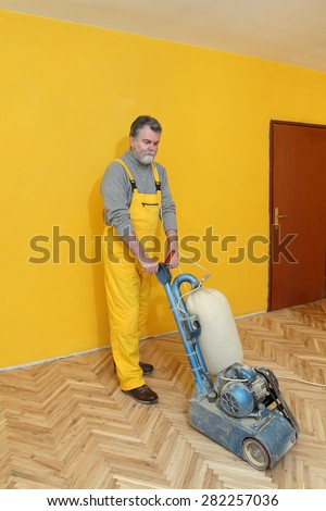 Worker polishing, sanding old parquet floor with grinding machine - stock photo