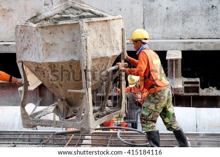 worker pouring cement during his working time