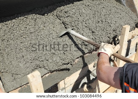 Worker pouring concrete to formwork at construction site - stock photo
