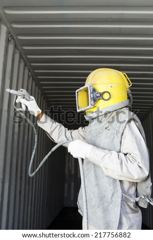 Worker prepare spray painting color inside wall container box steel - stock photo