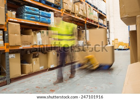 Worker pulling trolley with boxes in a blur in a large warehouse