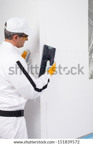 Worker rasping the corners of insulation panels - stock photo