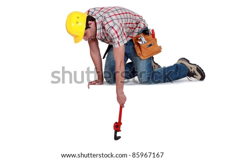 Worker reaching down with a wrench