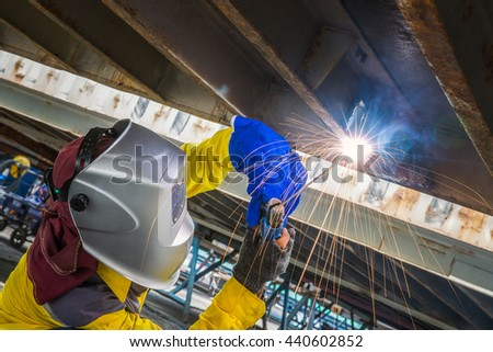 Worker repair the damage bottom side of container , Industrial Worker at the factory welding closeup - stock photo
