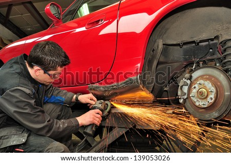 Worker repairing car body.