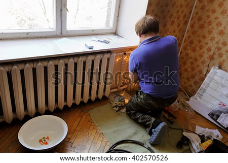 Worker replaces domestic radiator in the living room