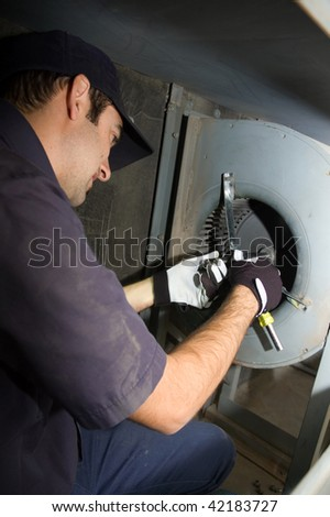 Worker replacing bearings in make up air unit. - stock photo