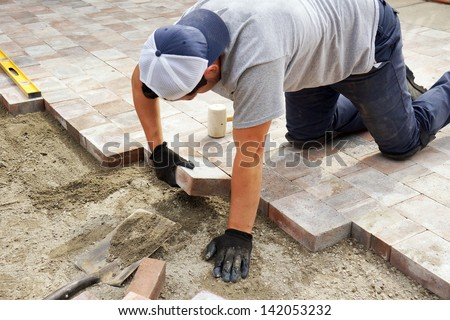 Worker setting paver bricks on large patio, paving backyard - stock photo