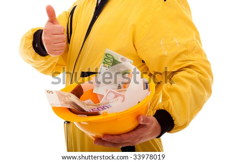 worker showing his helmet full of money - stock photo
