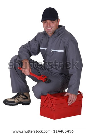 Worker sitting on a toolbox - stock photo