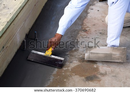 Worker smoothing freshly poured concrete for a cricket. - stock photo