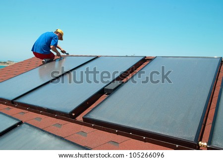 Worker solar water heating panels on the roof. - stock photo