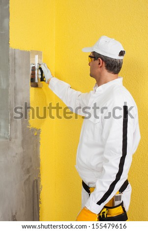 Worker spreading a plaster on a corner-wall - stock photo