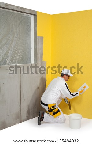 Worker spreading a plaster on a wall - stock photo