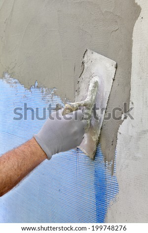 Worker spreading  mortar over styrofoam insulation and mesh  with trowel