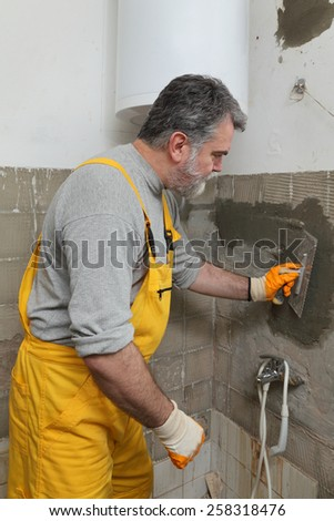 Worker spreading mortar with trowel to wall in a bathroom - stock photo