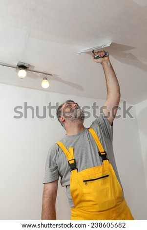Worker spreading  plaster to ceiling with trowel, repairing works - stock photo