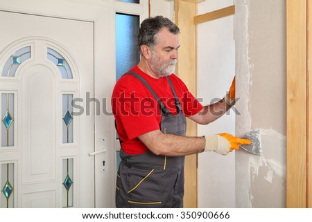 Worker spreading plaster with trowel to gypsum board and fiber mesh - stock photo