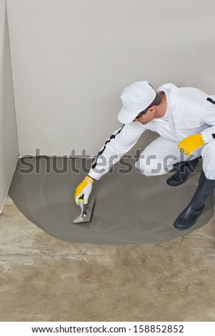 Worker spreading self leveling compound with trowel - stock photo
