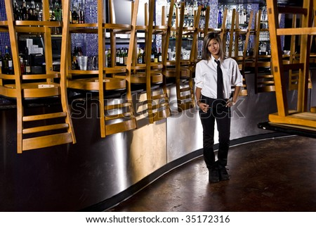 Worker standing next to bar of closed restaurant - stock photo