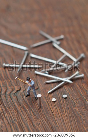 Worker sticks nail. Hard work concept. - stock photo