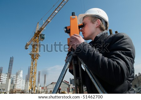 worker surveyor measuring distances, elevations and directions on construction site by theodolite level transit equipment - stock photo