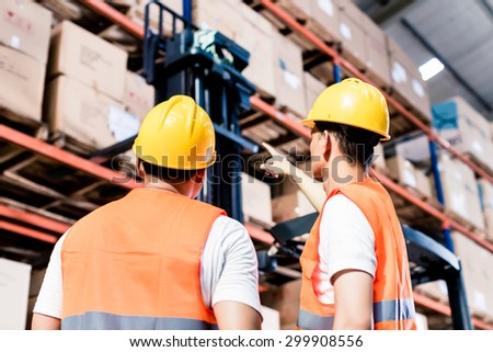 Worker team taking inventory in logistics warehouse - stock photo