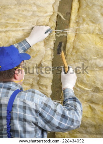 Worker thermally insulating a house attic using mineral wool - stock photo