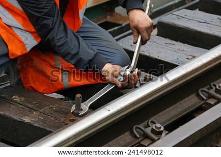 Worker tightens the screw on railroad with two spanners in hands - stock photo