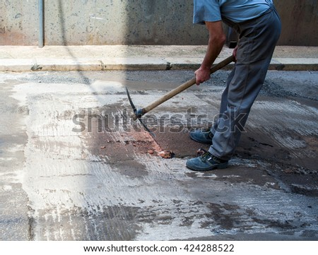 Worker use pickaxe fix cast iron manhole covers for a new telephone and electricity cable. Selective focus and motion blur.