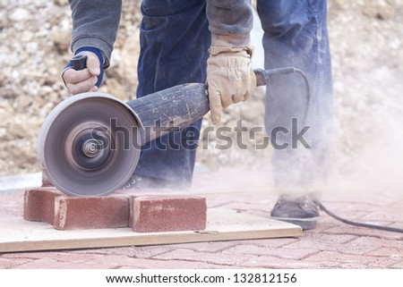 worker uses a stone cutter to cut the brick pavers - stock photo