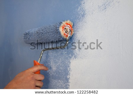 worker using a paint roller - stock photo