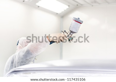Worker using a paint spray gun for painting a car in a special booth - stock photo