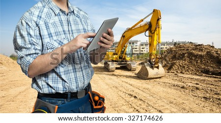 Worker using a tablet in a construction site - stock photo