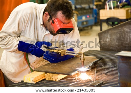 Worker using an acetylene torch to cut through metal in a metalworks factory. - stock photo