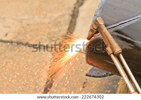 Worker using an Gas cutting torch to cut through metal in factory. - stock photo