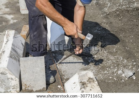 Worker using chisel and hammer for paving work. Selective focus and shallow dof. - stock photo