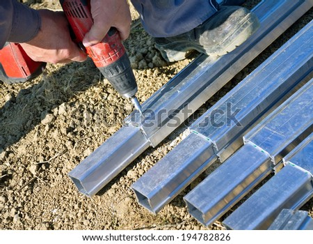 Worker using electric screwdriver for fixing aluminum construction frames on construction site - stock photo