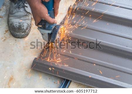 Worker Using Grinding Machine To Cut Metal Roof