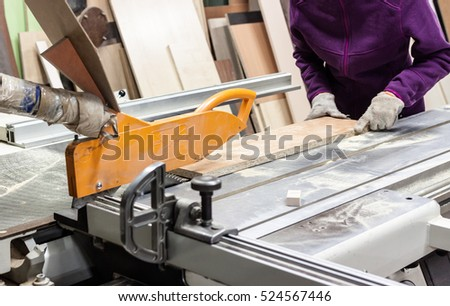 Worker using saw machine to make furniture at carpenter`s workshop. Handmade business at small furniture factory.