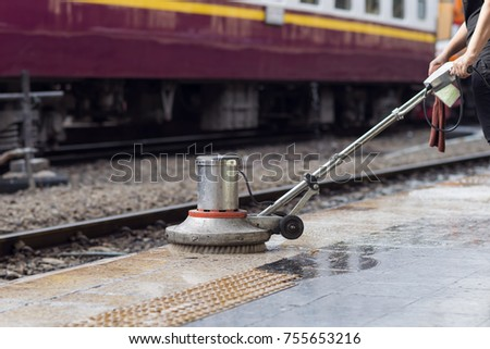 Worker Using Scrubber Machine For Cleaning And Polishing Floor. Cleaning  Maintenance Train At Railway Station