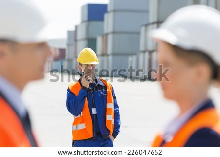 Worker using walkie-talkie while colleagues discussing in foreground at shipping yard - stock photo