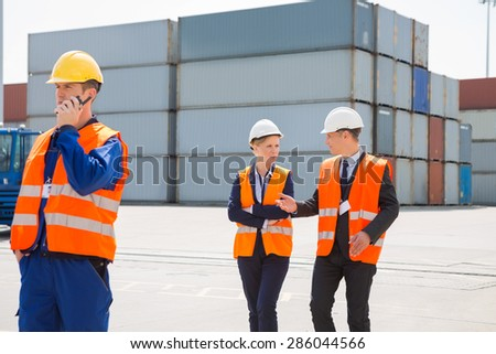 Worker using walkie-talkie while colleagues discussing in shipping yard - stock photo